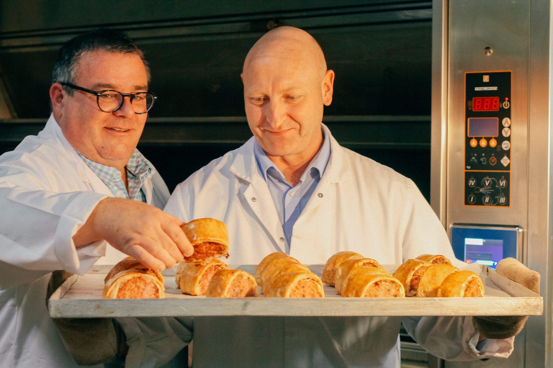 Simon Thomas and Steve Cockayne from Thomas the Baker inspecting the award-winning Deli Black Pudding Sausage Rolls