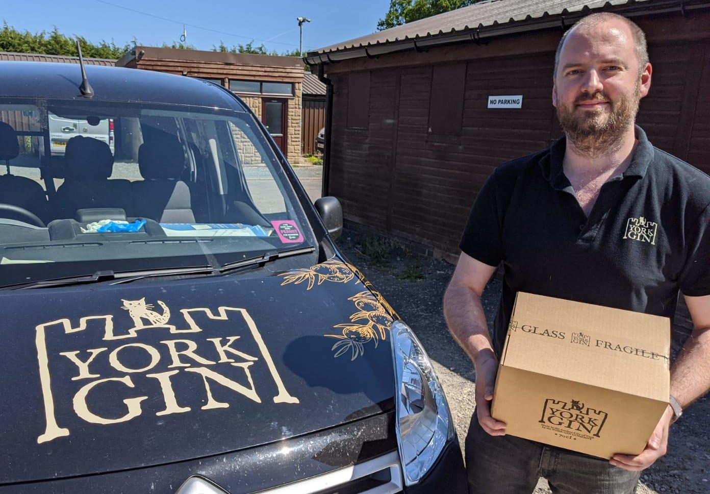 Harry next to York Gin van and holding box with paper tape